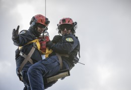 Two National Guard team members dangle from a cable below a helicopter